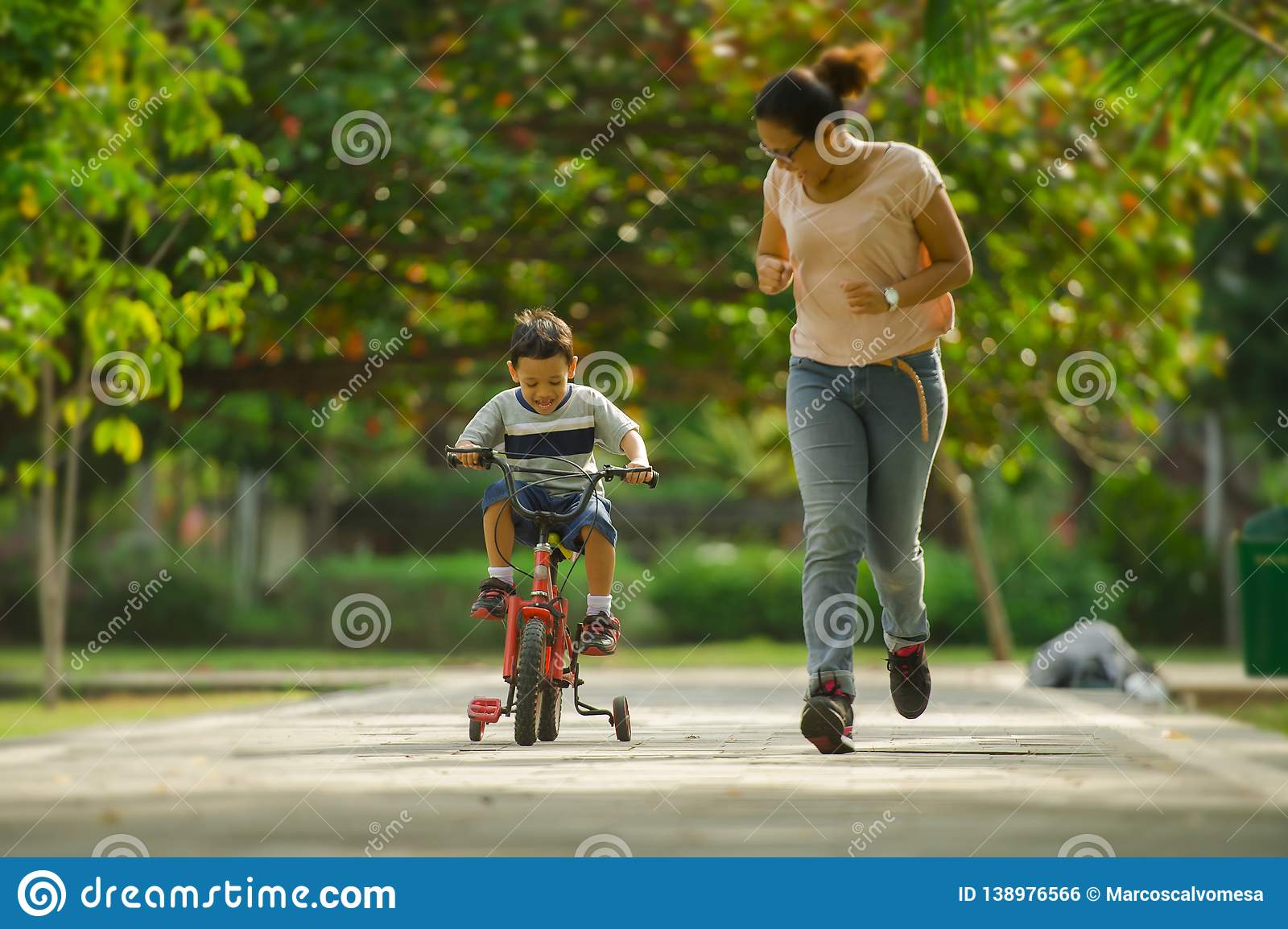 Lifestyle portrait of Asian Indonesian mother and young happy son at city park having fun together the kid learning bike riding. And the women running after the royalty free stock image