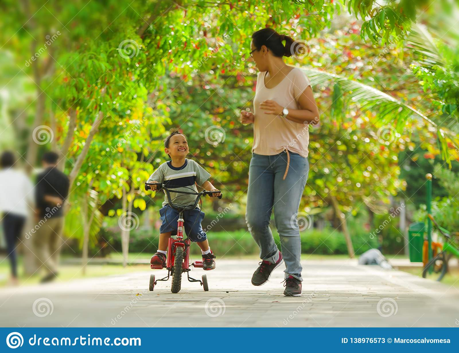 Lifestyle portrait of Asian Indonesian mother and young happy son at city park having fun together the kid learning bike riding. And the women running after the stock photos