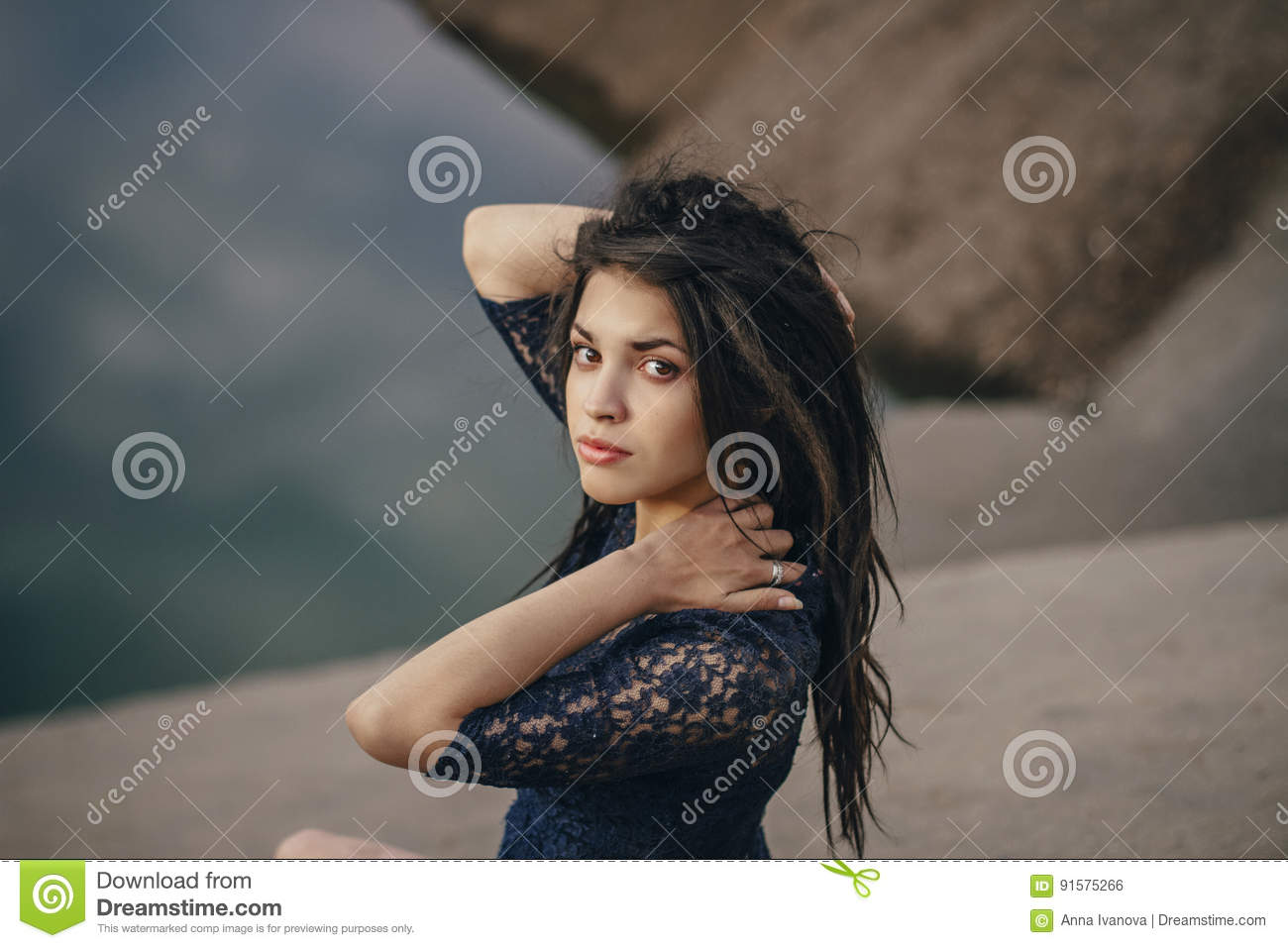 Lifestyle portrait of a woman brunettes in background of lake sitting in sand on a cloudy day. Romantic, gentle, mystical