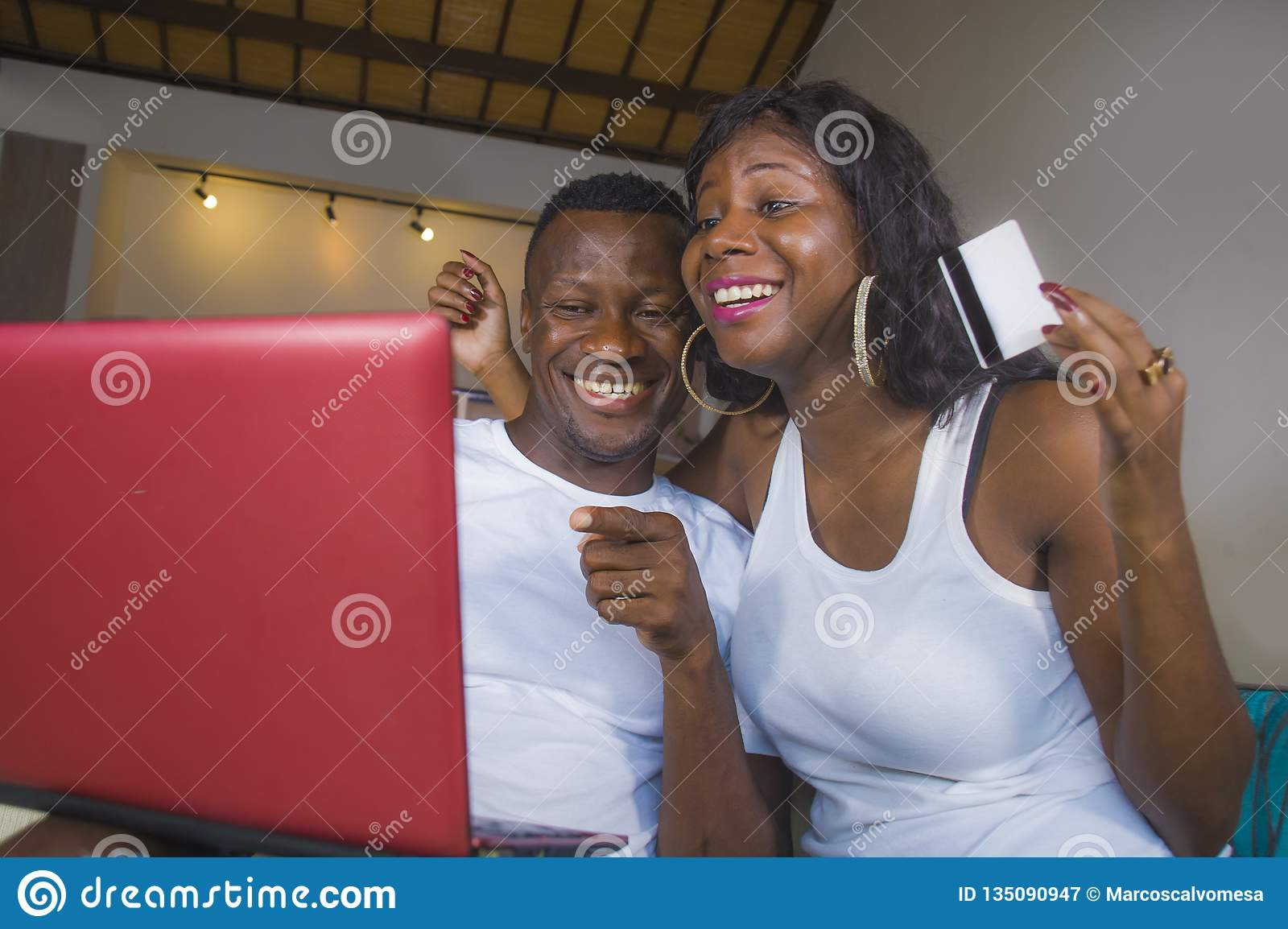 Lifestyle portrait of young happy and attractive black afro American couple enjoying at home using credit card and laptop computer