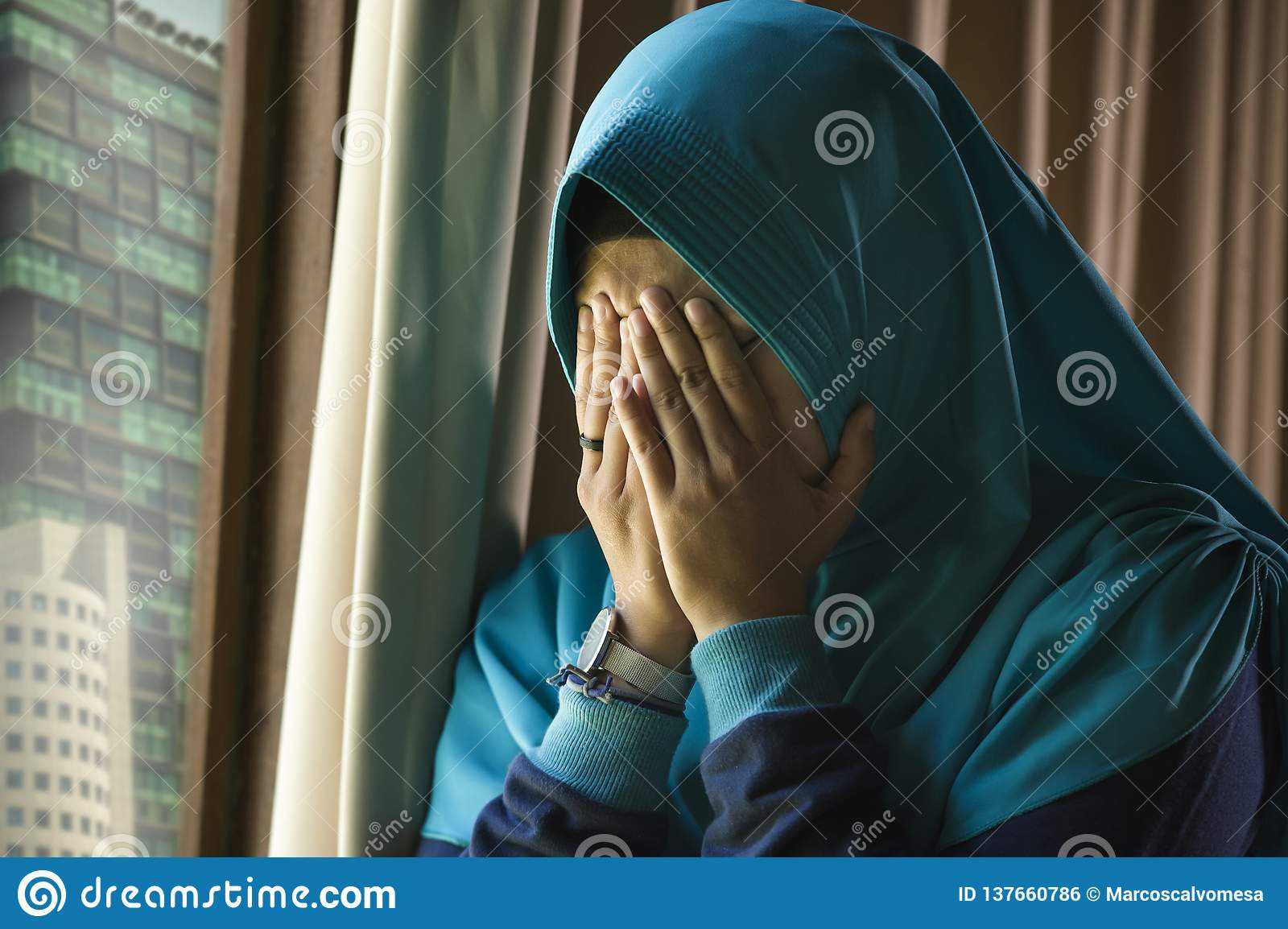 Young sad and depressed Muslim woman in Islam traditional Hijab head scarf at home window feeling unwell suffering depression