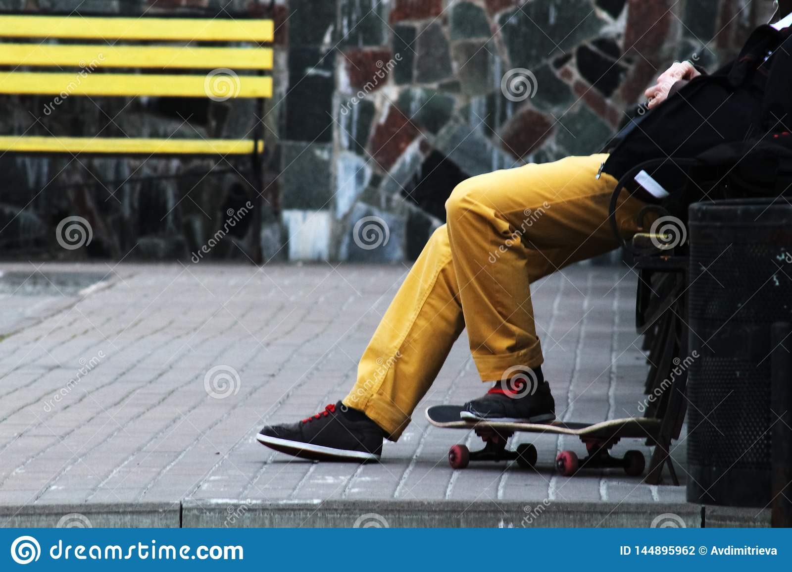 Lifestyle Relax Hipster Concept. Man Skateboarder in yellow jeans relaxing on bench. Yellow bench and stone background