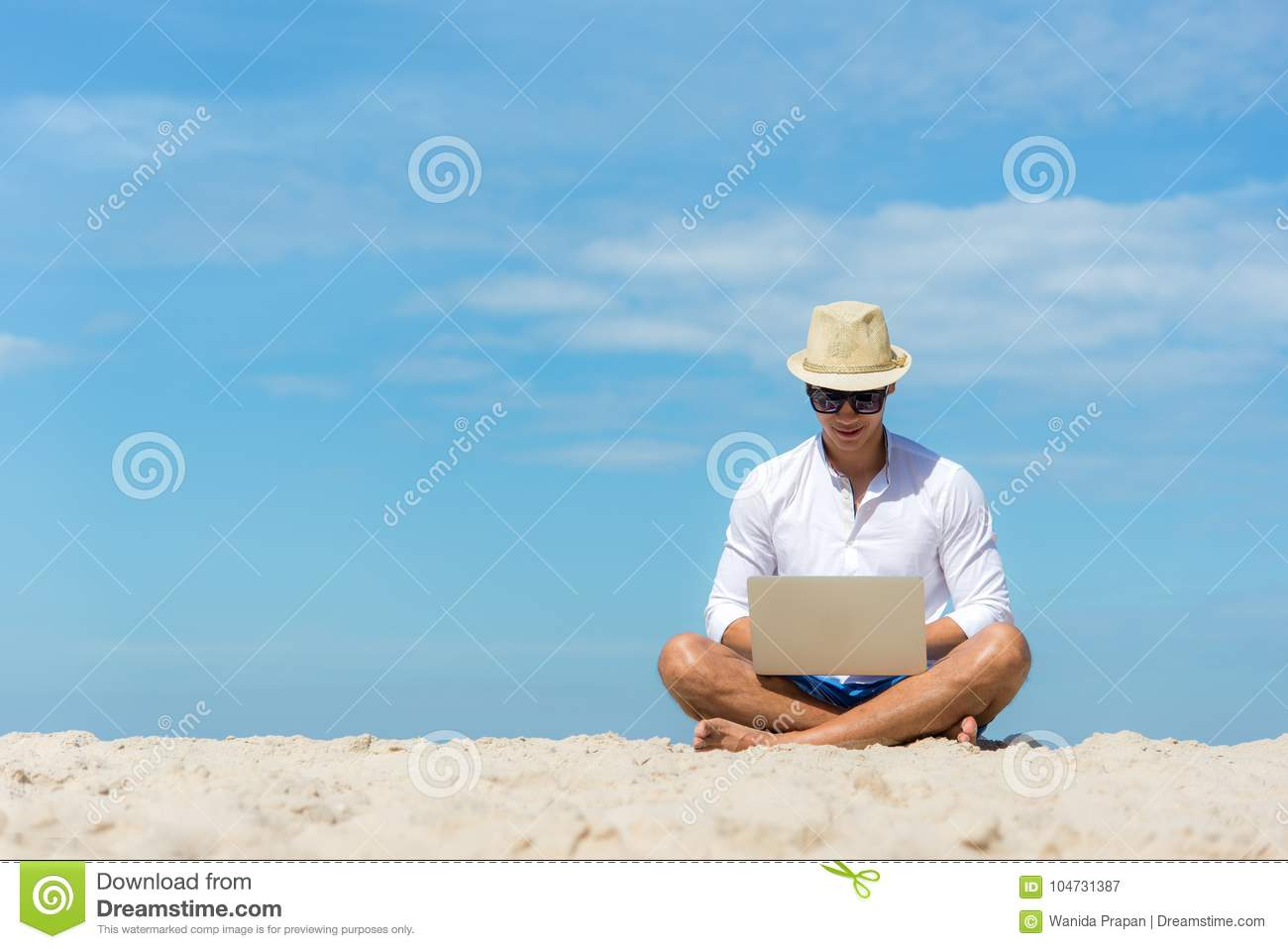 Lifestyle young asian man working on laptop while sitting on the beautiful beach, freelance working on holiday summer, blue sky ba