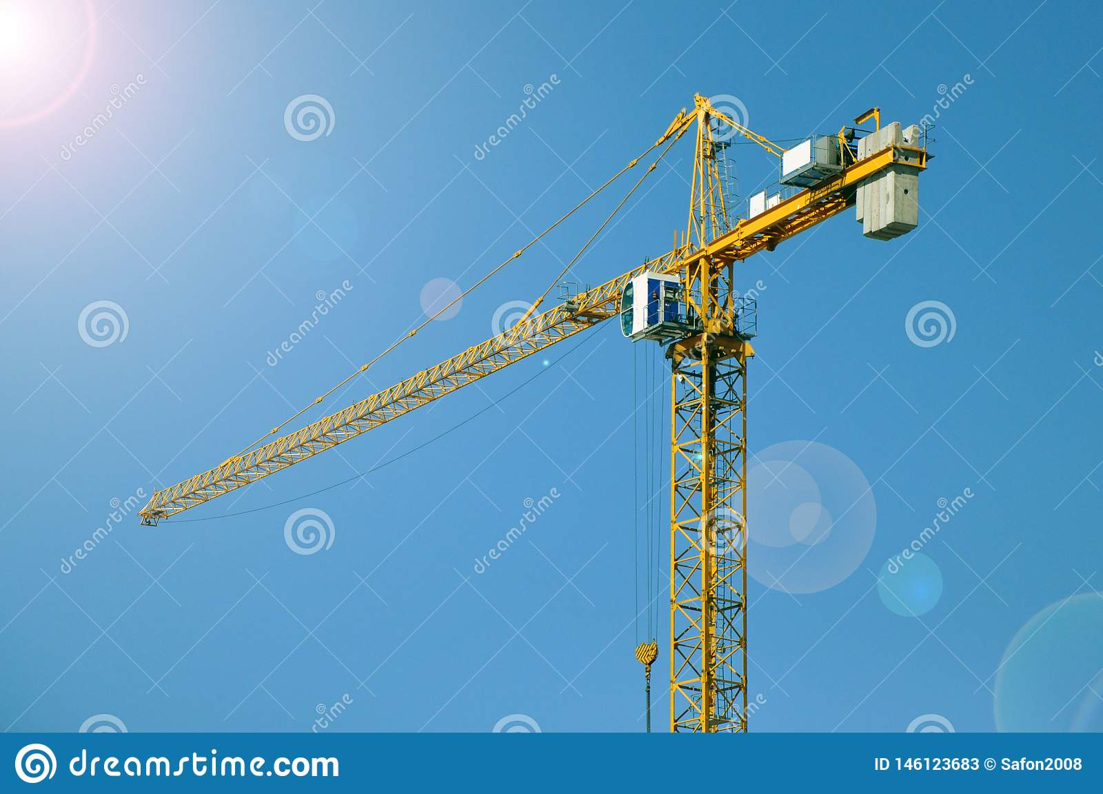 Lifting tower crane against the blue sky