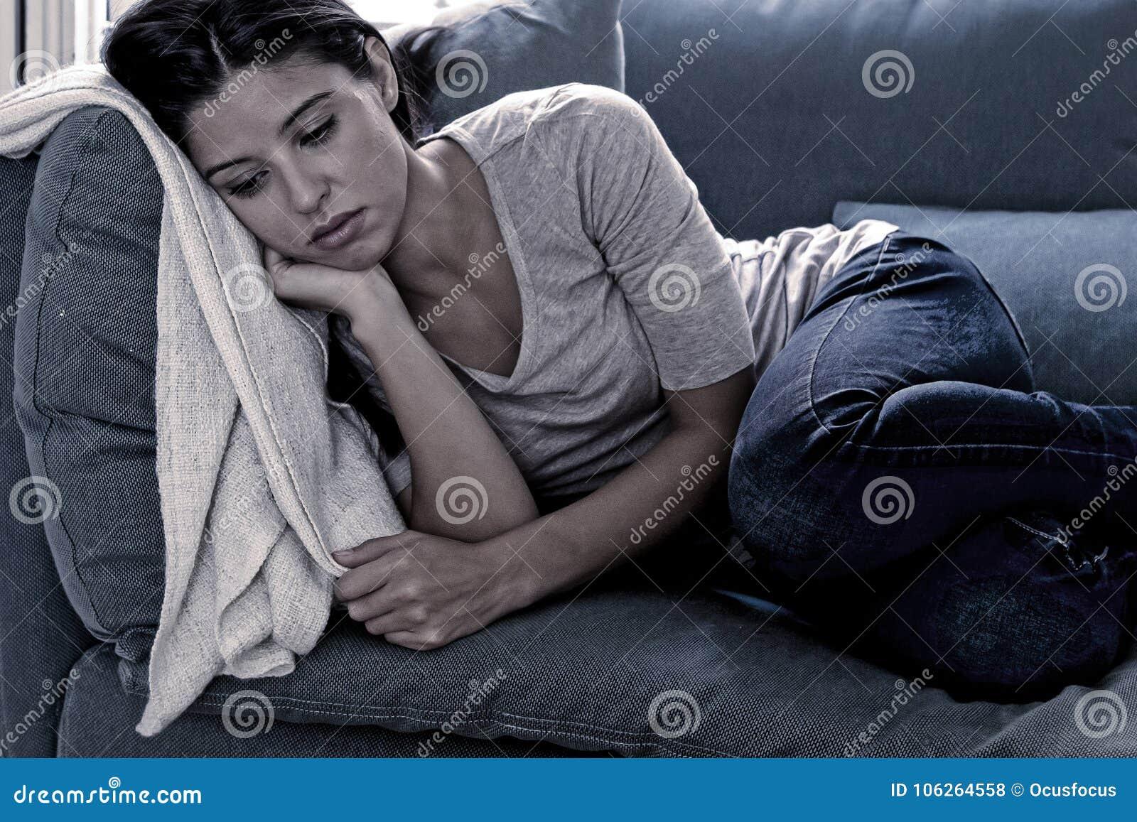 Liggande hemmastadd vardagsrumsoffa för ung attraktiv latinsk kvinna som tröttas och oroas lida fördjupningen som känner sig leds