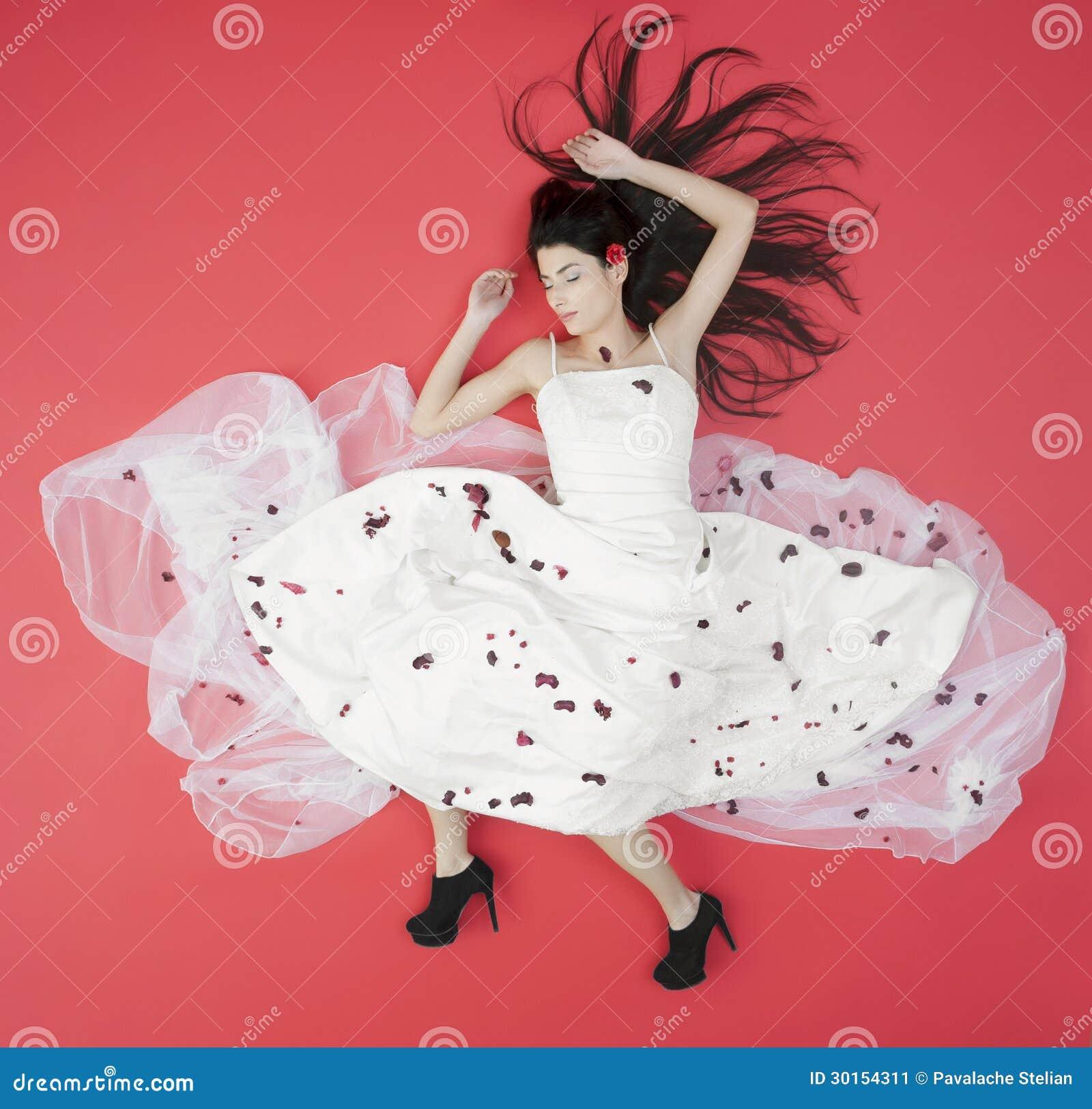 Liggande skönhetbrud i den vita klänningen som isoleras på rött