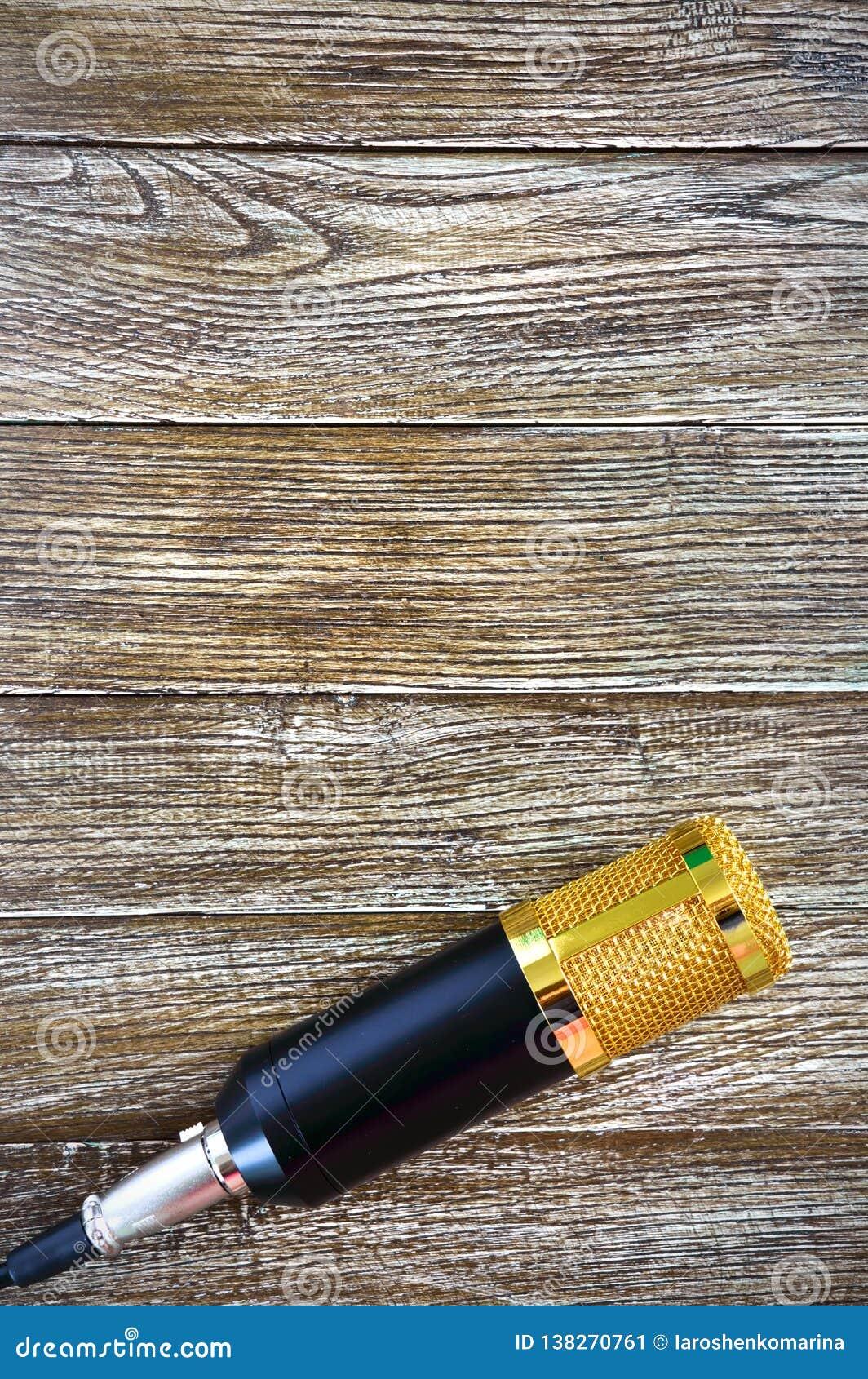 Ligger den guld- mikrofonen för kondensatorn på en trätabell med kopieringsutrymme musikaliskt tema Lekmanna- lägenhet