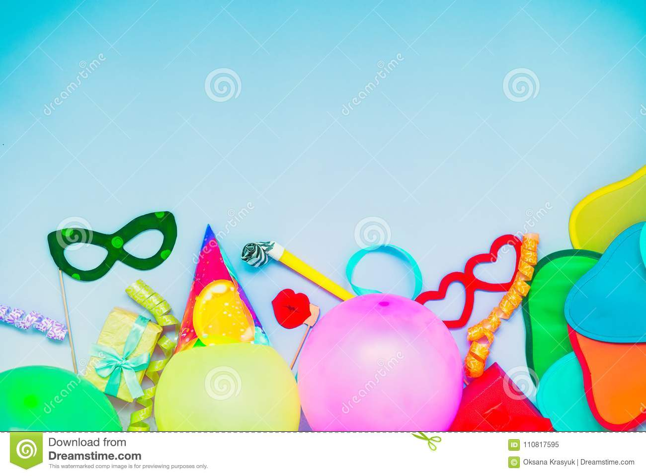 Light blue Festive background with party tools and decoration - baloons, funny carnival masks, festive tinsel. Happy birthday gree