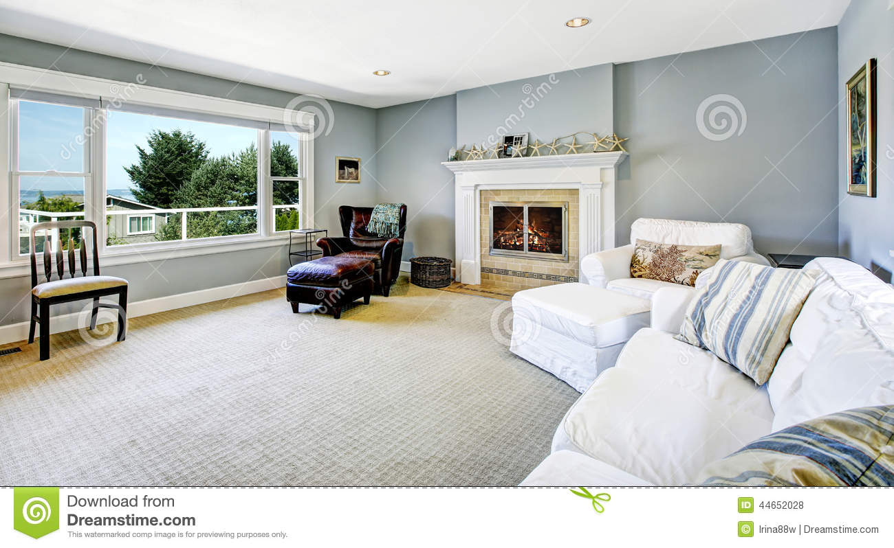 light blue living room with white sofa and fireplace stock