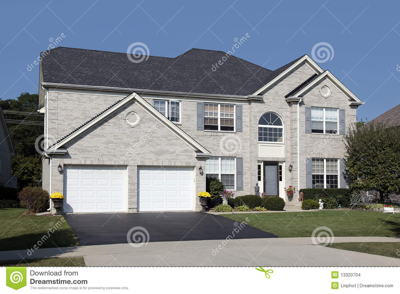 Light Brick Home With Double Arched Garage Stock Photo