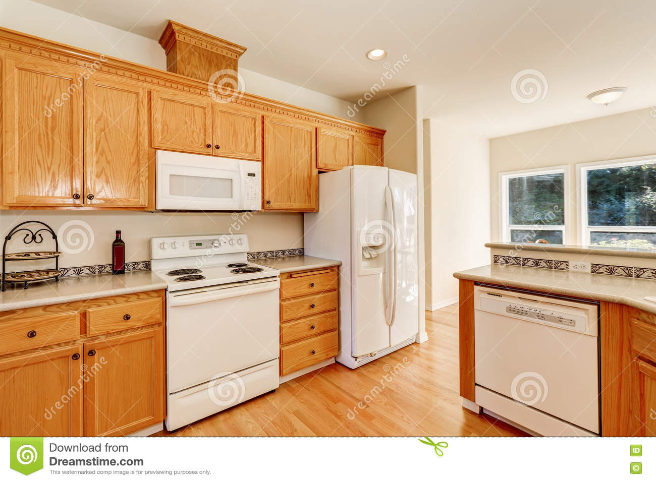 Light Brown Kitchen Cabinets And White Appliances Stock