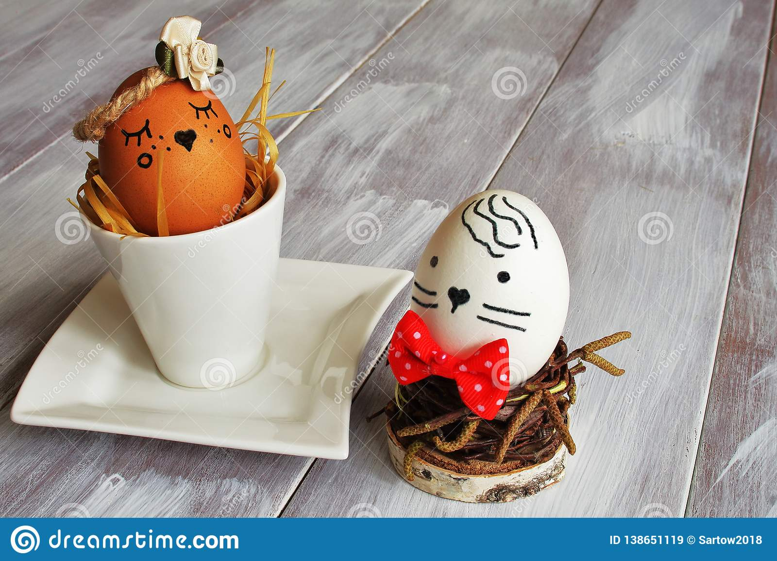 Light brown selfish egg with satin flower in exclusive porcelain coffee pair and white egg with red tie nest from birch twigs on