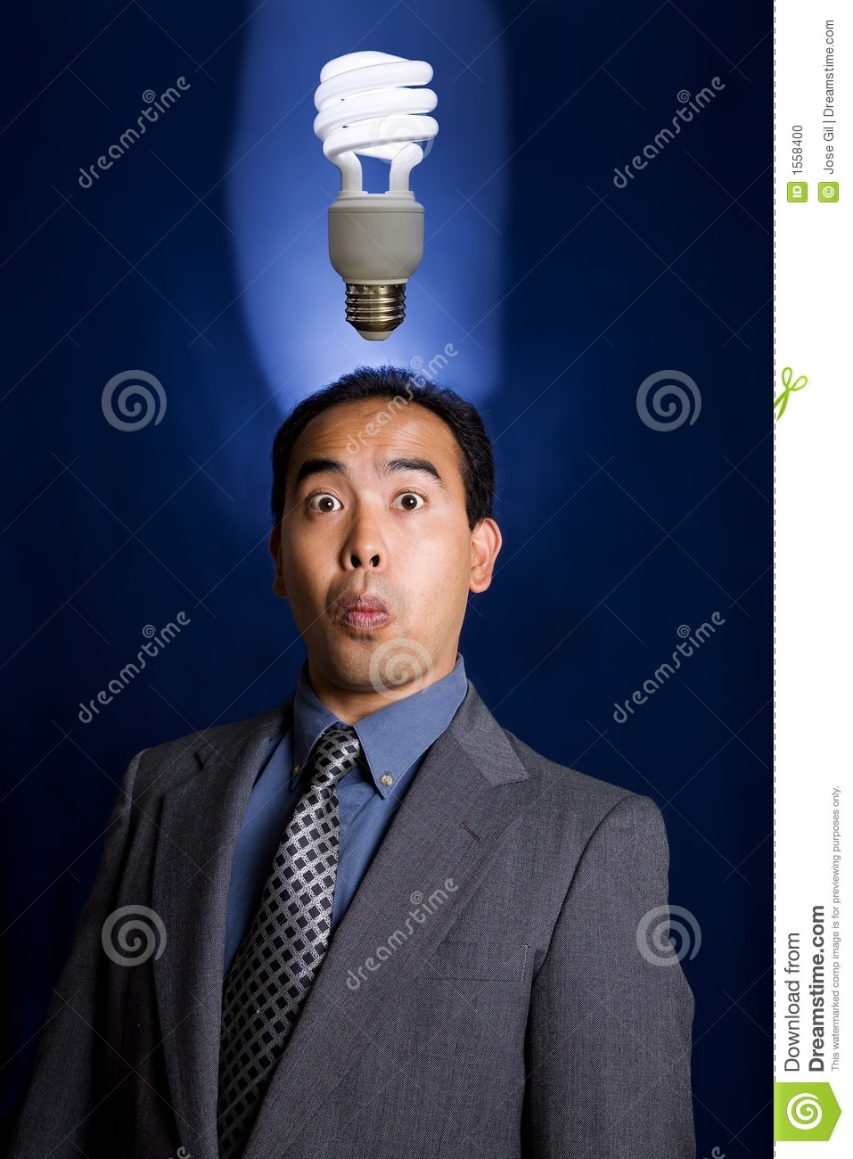 Business Man Of Asian Descent Having And Idea As Shown By A Ecofriendly Compact Fluorescent Light Bulb Above His Head