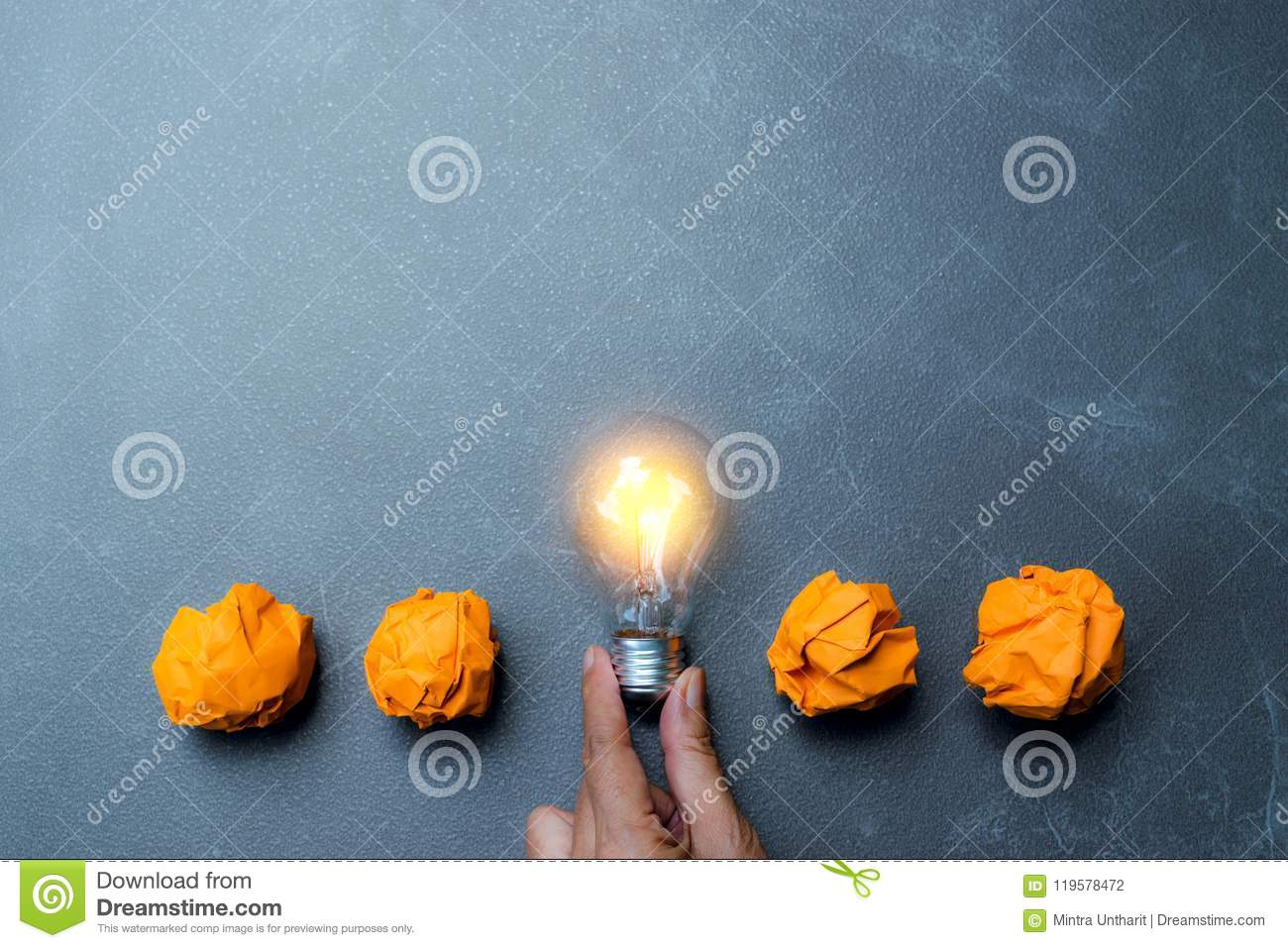 Hand holding light bulb put in the middle of orange papers it for idea,energy,solar concept.
