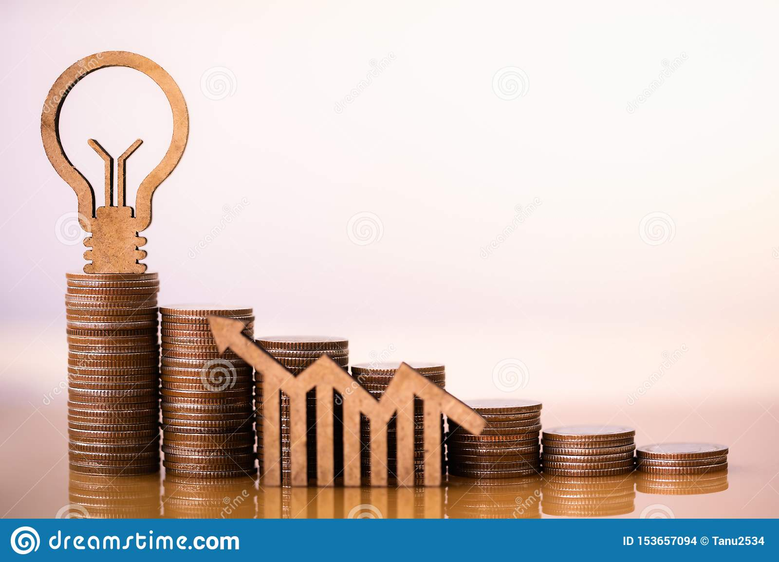 Light bulb and stack of coins in concept of savings and money growing or energy save.