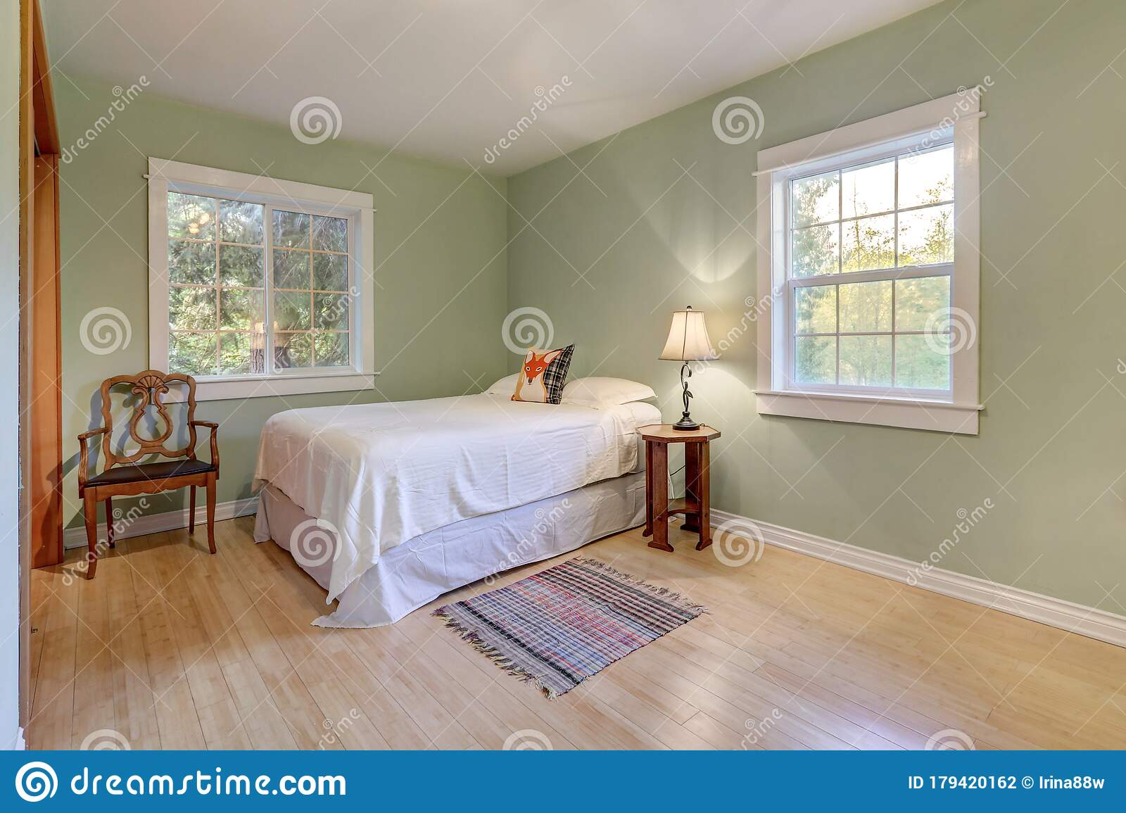 Light Green Walls Bedroom Interior With Two Windows And Light Hardwood Floor With White Bed And Antique Chair And Casual Rug Stock Photo Image Of Clean Beige 179420162