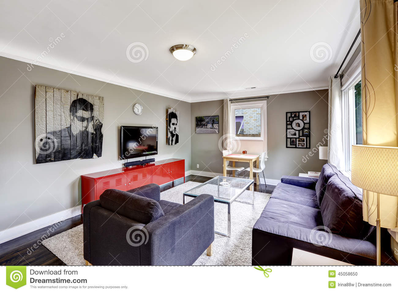 Light Grey Living Room With Bright Red Cabinet And Black Furnitu Stock Photo