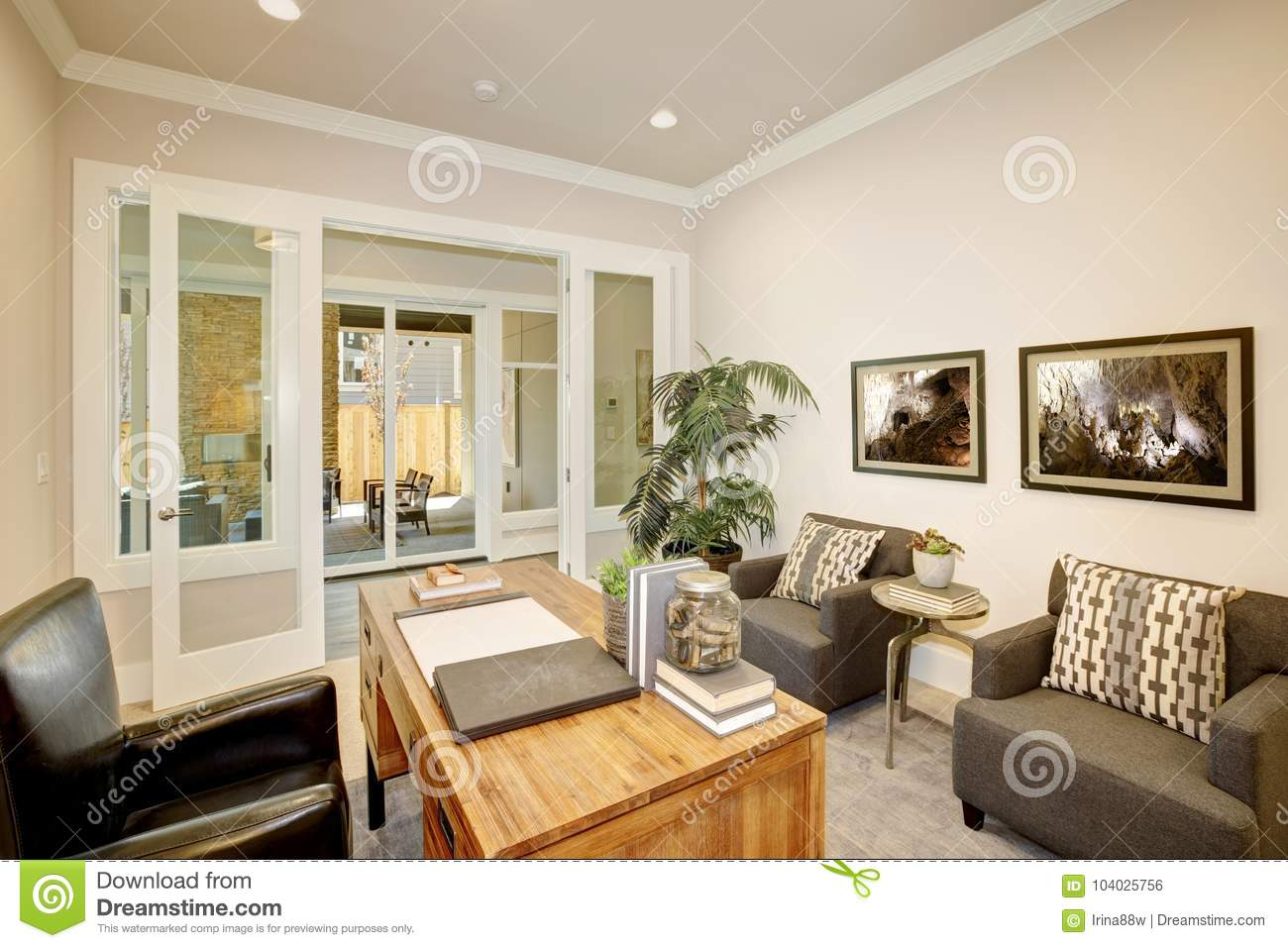 Light Home Office Features A Wooden Desk Placed In The Center Of The Room  On A Gray Rug In Front Of Two Comfortable Armchairs Topped With Geometric  White ...