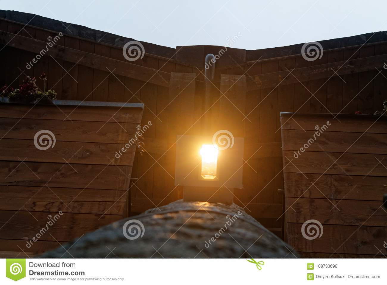 Light Lamp Under The Wooden Roof With Dark Wooden Beams