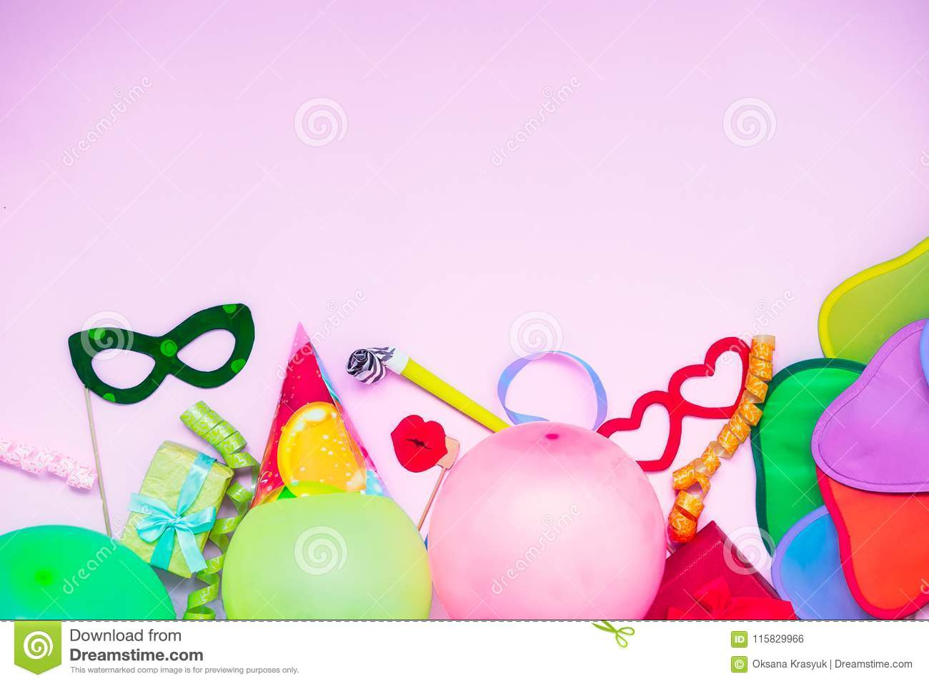 Light pink Festive background with party tools and decoration - baloons, funny carnival masks, festive tinsel. Happy birthday gree