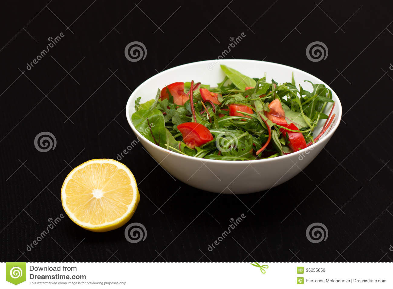 Light salad with tomatoes in white china bowl and lemon
