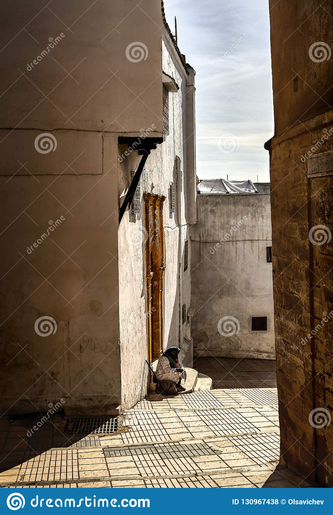 Light and shadow Sale. A street in the old city of Sale under the rays of the midday spring sun in front of a golden door