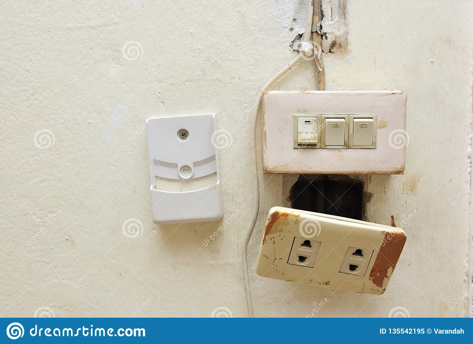 a light switch and electrical breaker with damaged wiring on the wall