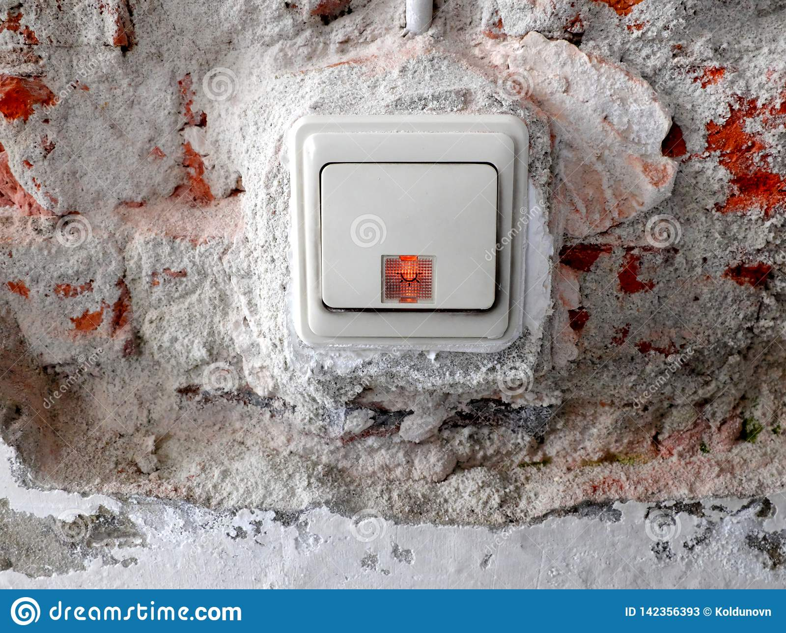 Light switch in a wall with removed plaster and visible bricks