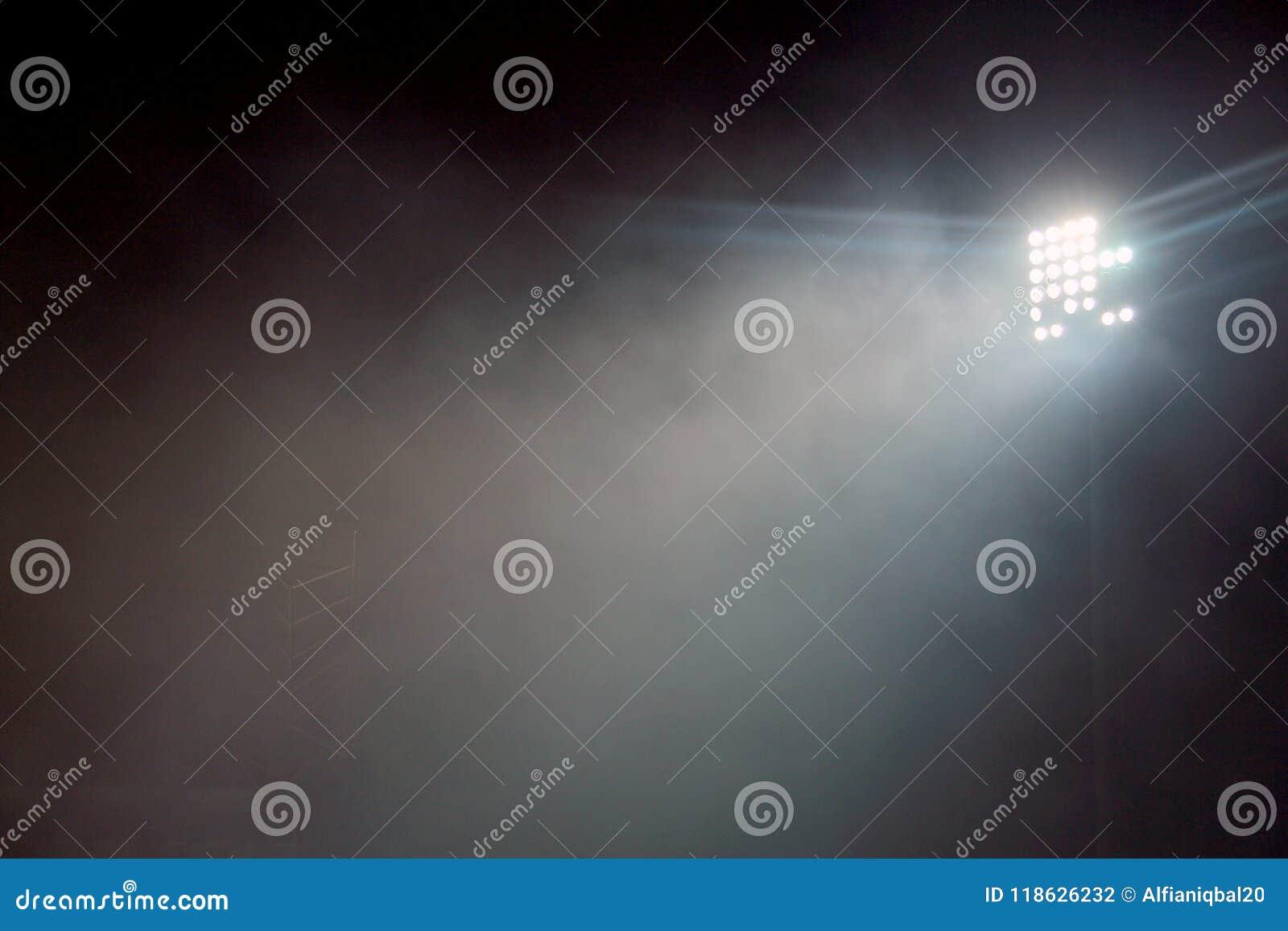 Light tower lit at a stadium during nightime. Stadium lights against dark night sky background. stadium lights and smoke