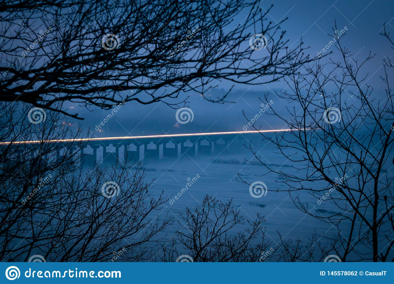 Light trail across the Susquehanna River Bridge, in the evening hours on a misty and foggy day, Columbia County, PA