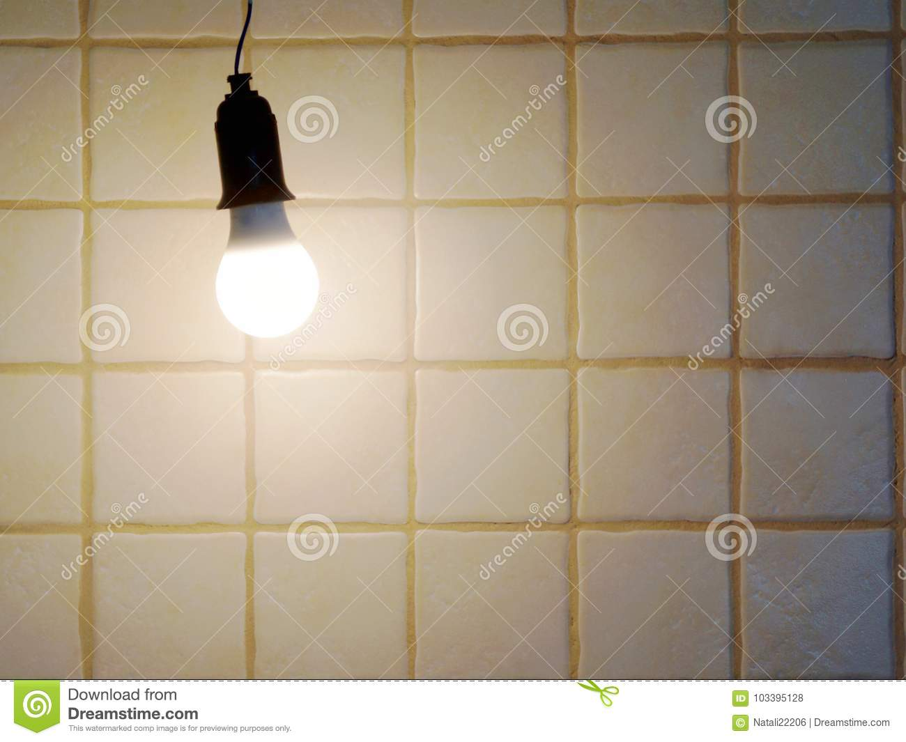 A Lighted Bulb On The Background Of A Wall Tiled Led Light Stock