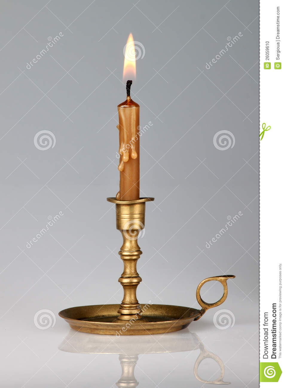Lighted Candle In An Old Brass Candlestick Stock Photo