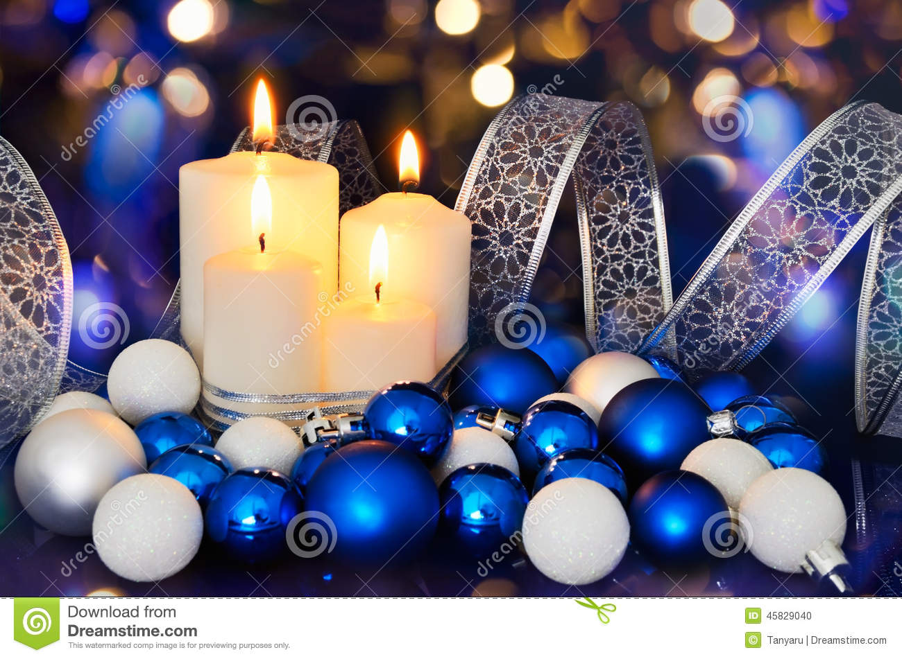 lighted candles and blue white christmas tree decorations on the