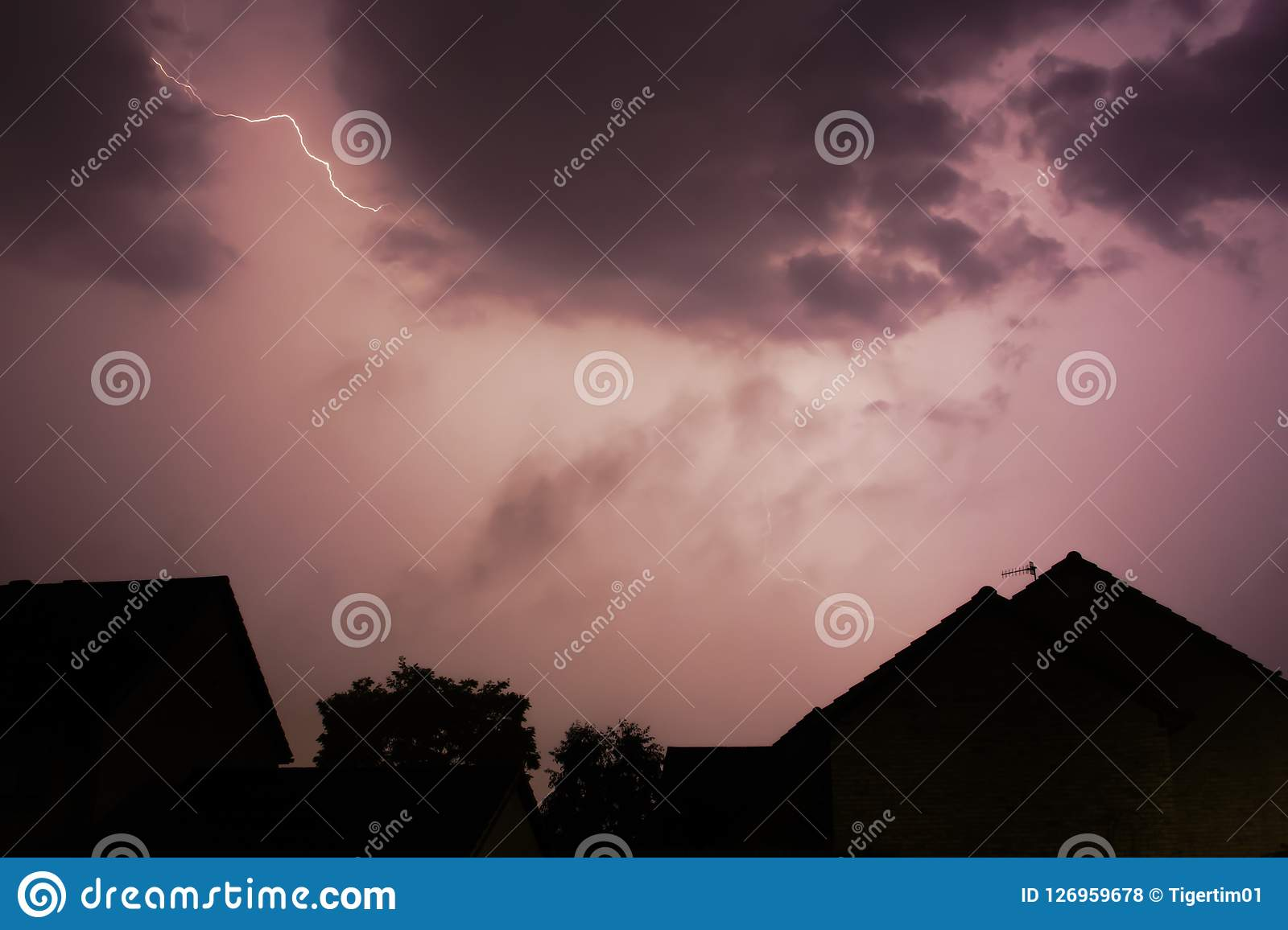 Lightening bolt over houses in the middle of a storm