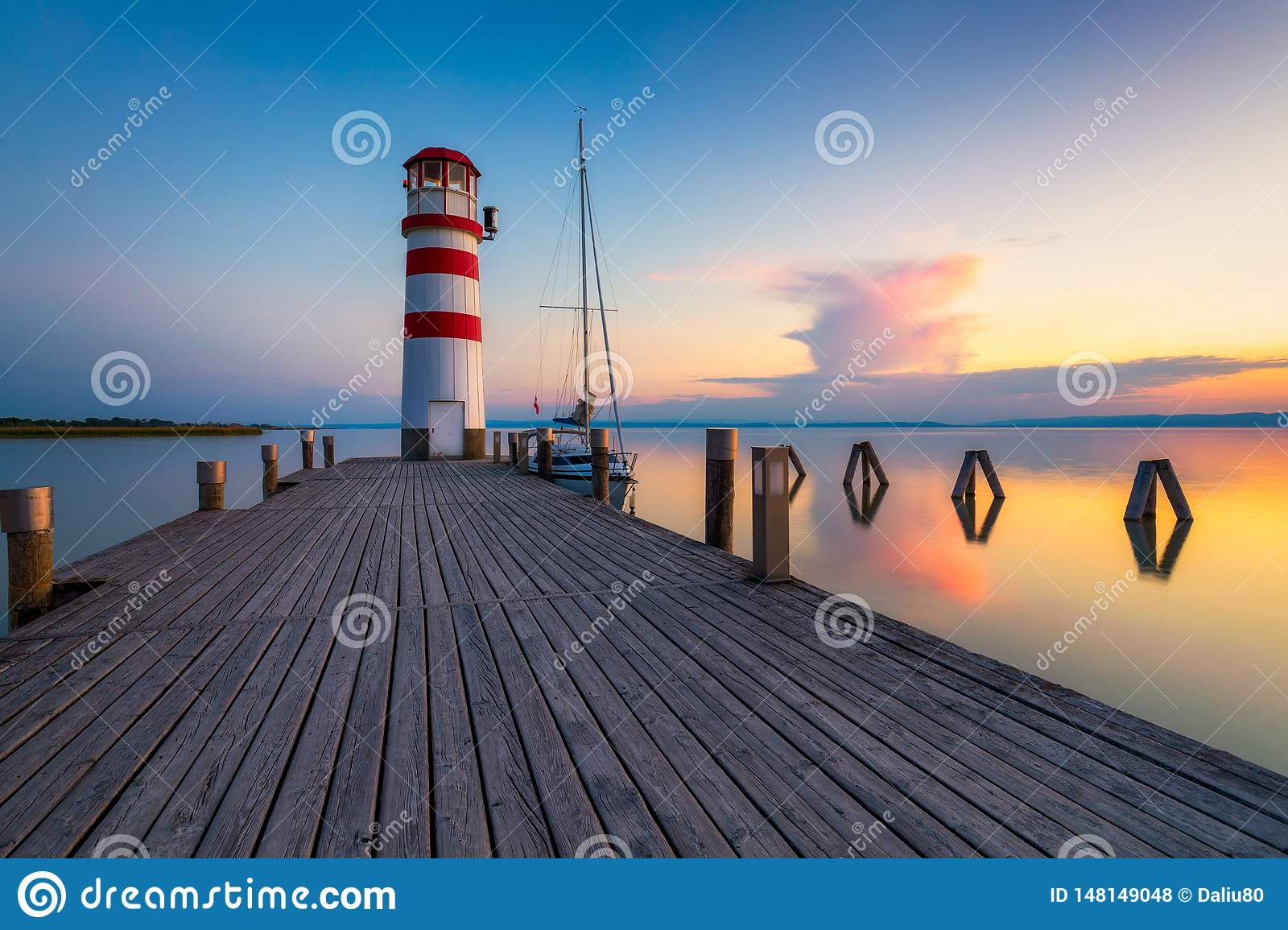Lighthouse at Lake Neusiedl, Podersdorf am See, Burgenland, Austria. Lighthouse at sunset in Austria. Wooden pier with lighthouse