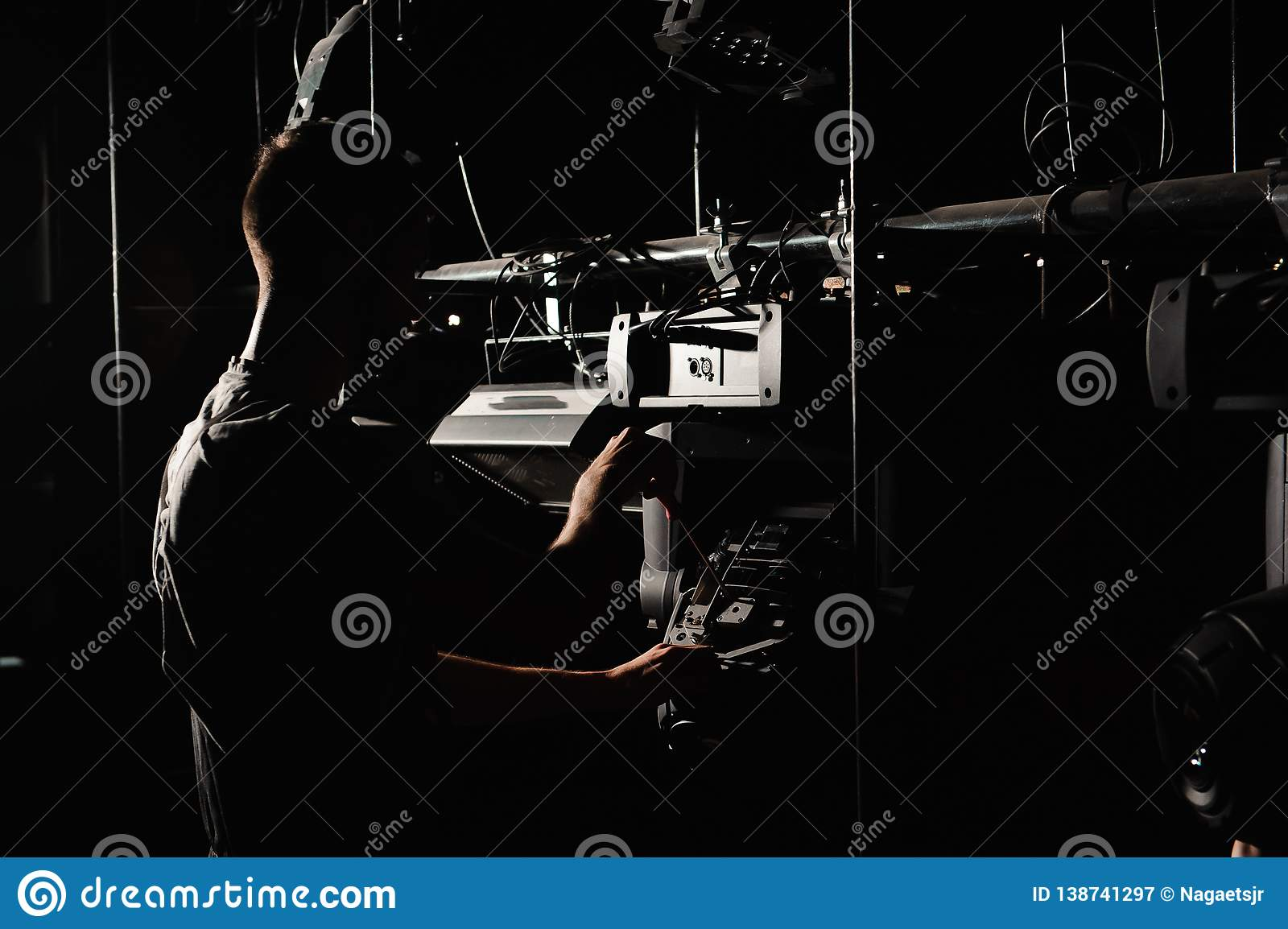 The lighting engineer repairs the light device on stage