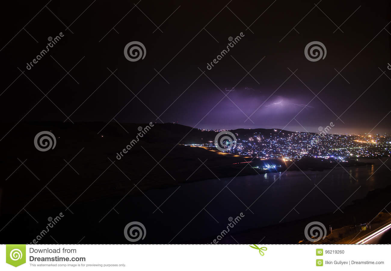 Lightning with dramatic clouds. Night thunder-storm over the mountain and the lake in Baku, Azerbaijan