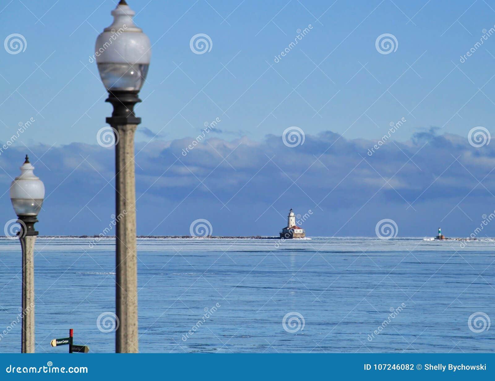 Lightpost in voorgrond met cloudscape over horizon van Meer Michigan op een bevriezende Januari-ochtend met bevroren meer