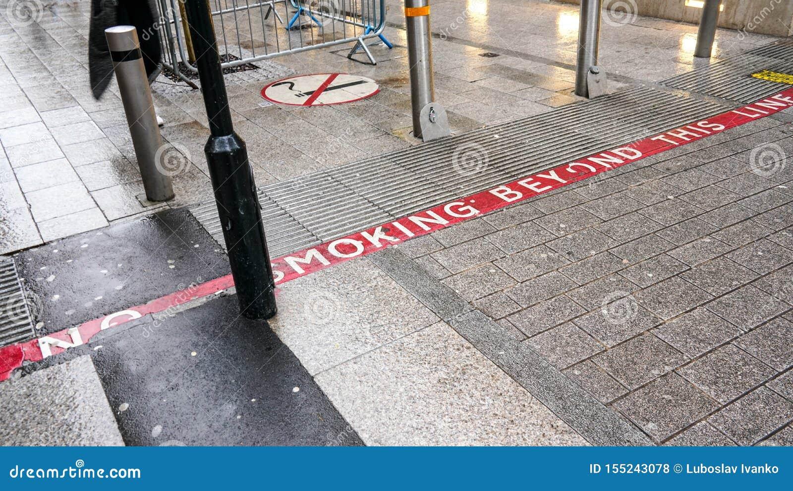 Ligne rouge sur le trottoir avec le texte NON-FUMEURS, signe près des piétons également de information ils entrent dans le secteu