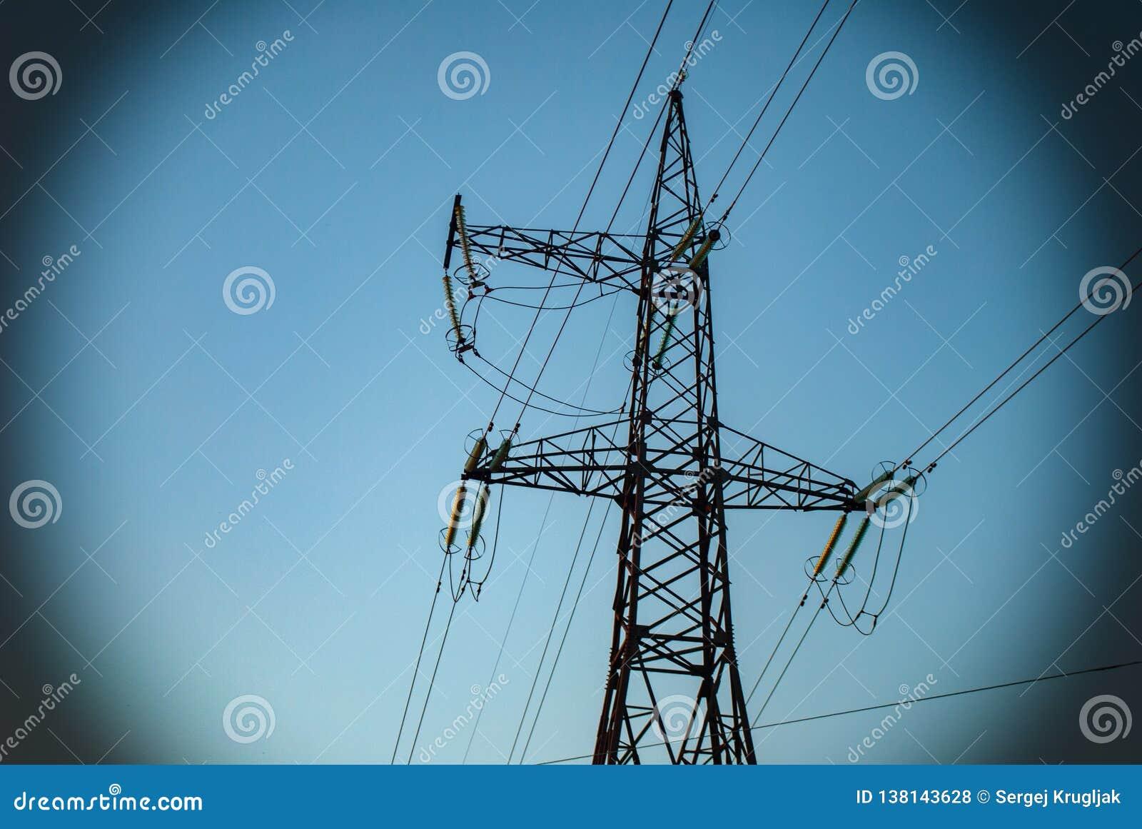 Lijn met hoog voltage met draden tegen een blauwe hemel