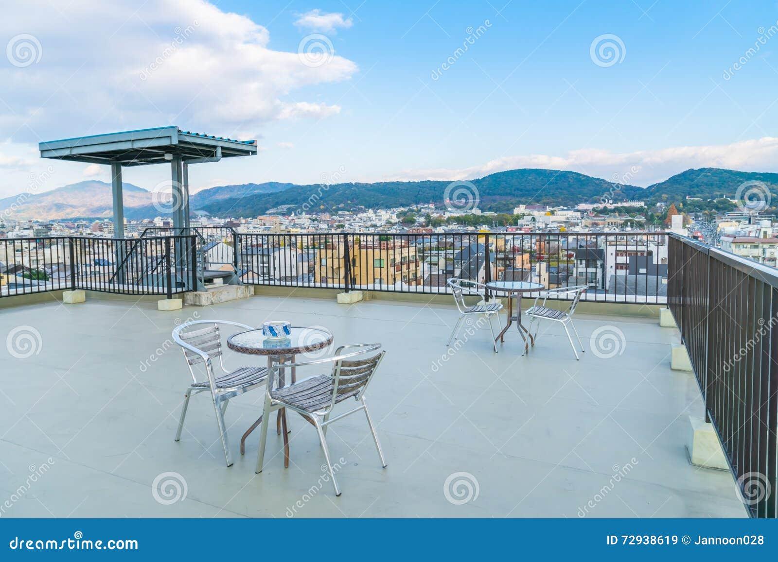 Lijst en stoelen op buitenkant van het dak de hoogste terras stock