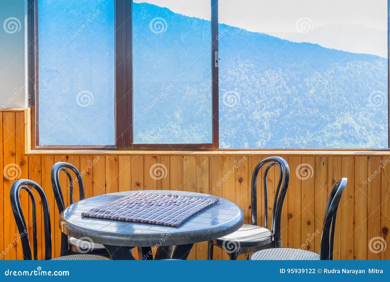 Lijst, stoelen en venster met buiten mening van berg