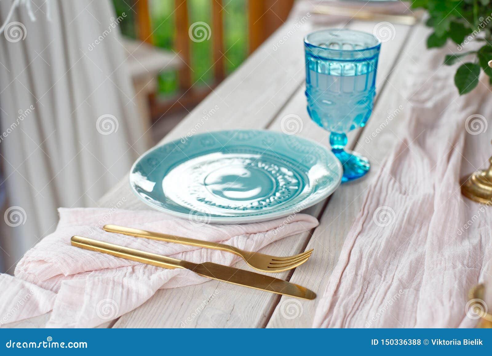 Lijst voor gasten, die met kaarsen worden verfraaid, die met bestek en aardewerk worden gediend en omvat met een tafelkleed blauw