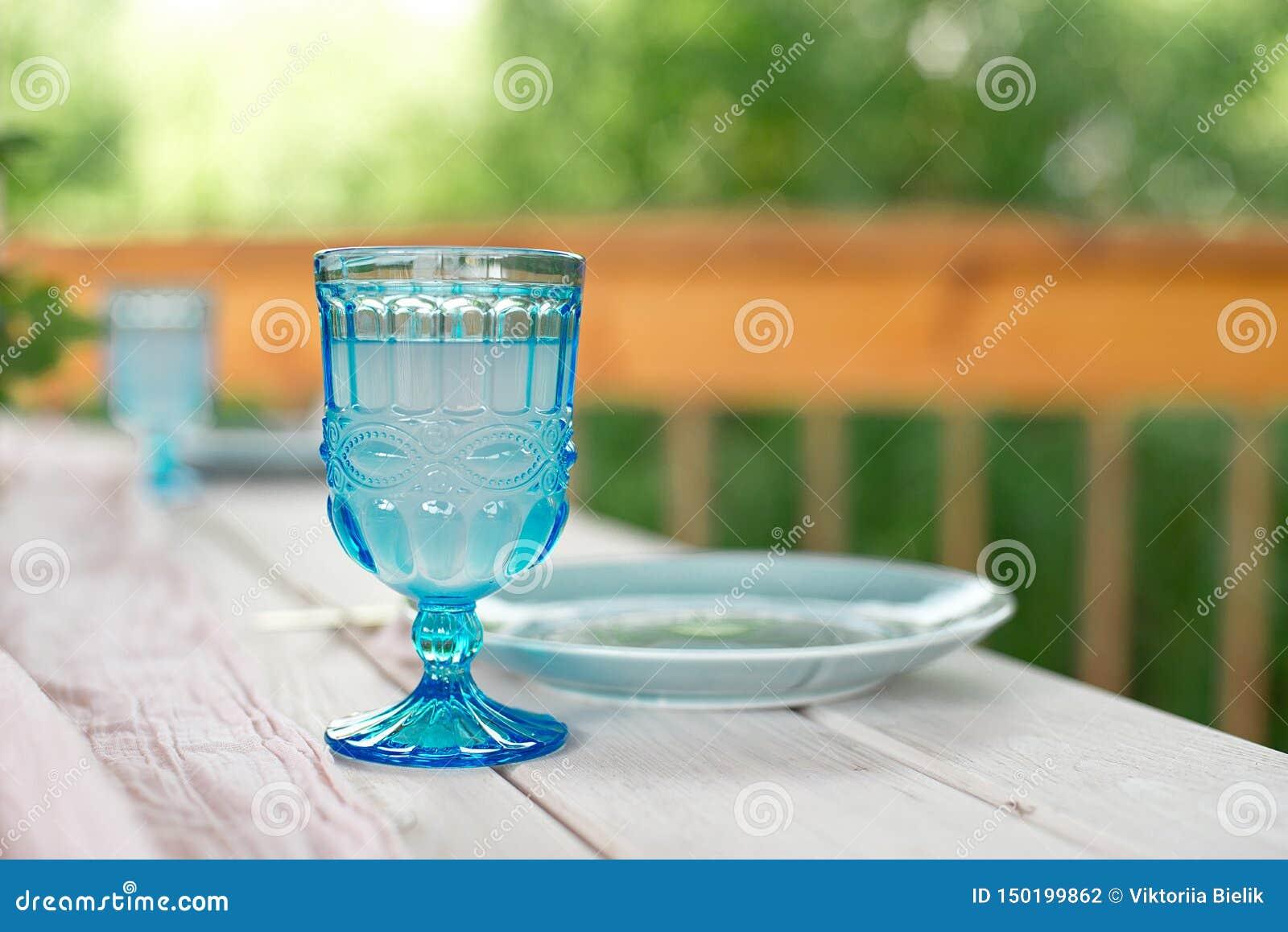 Lijst voor gasten, met kaarsen worden, met bestek en aardewerk worden gediend verfraaid die en omvat met een tafelkleed blauwe pl