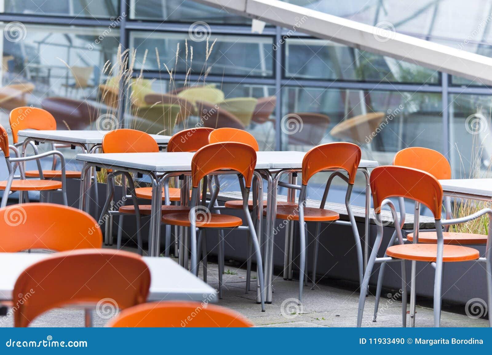 Gekleurde Eettafel Stoelen.Lijsten En Gekleurde Stoelen In Een Straatkoffie Stock Foto