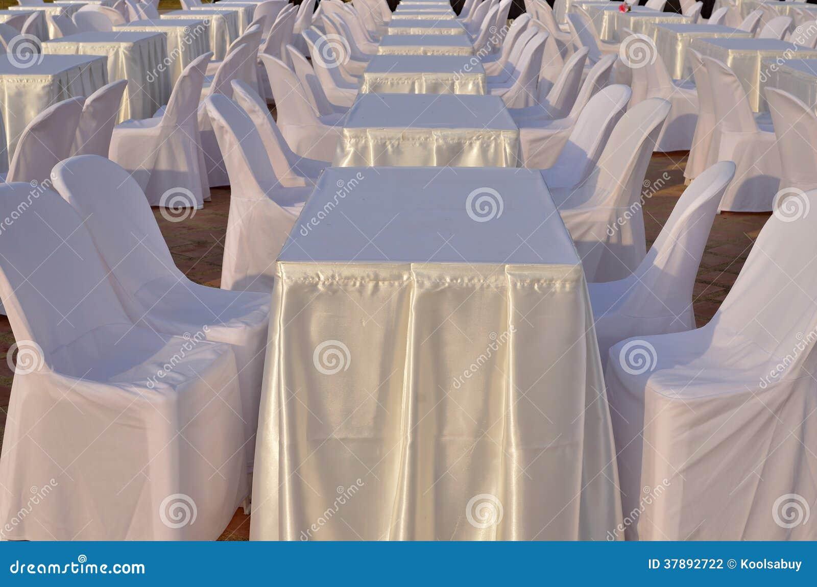 Lijsten en stoelen met witte kleren.