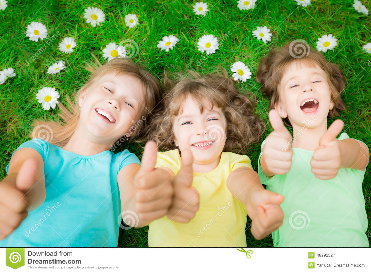 Happy Children Lying On Green Grass In Spring Park Laughing Kids Showing Thumbs Up