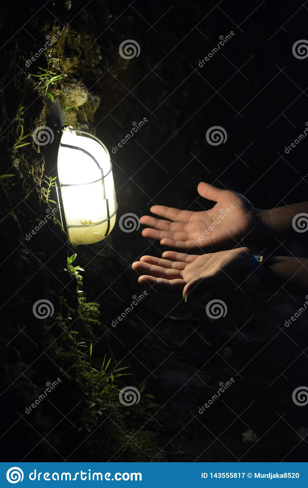 Like the position of the hands praying under the lamp