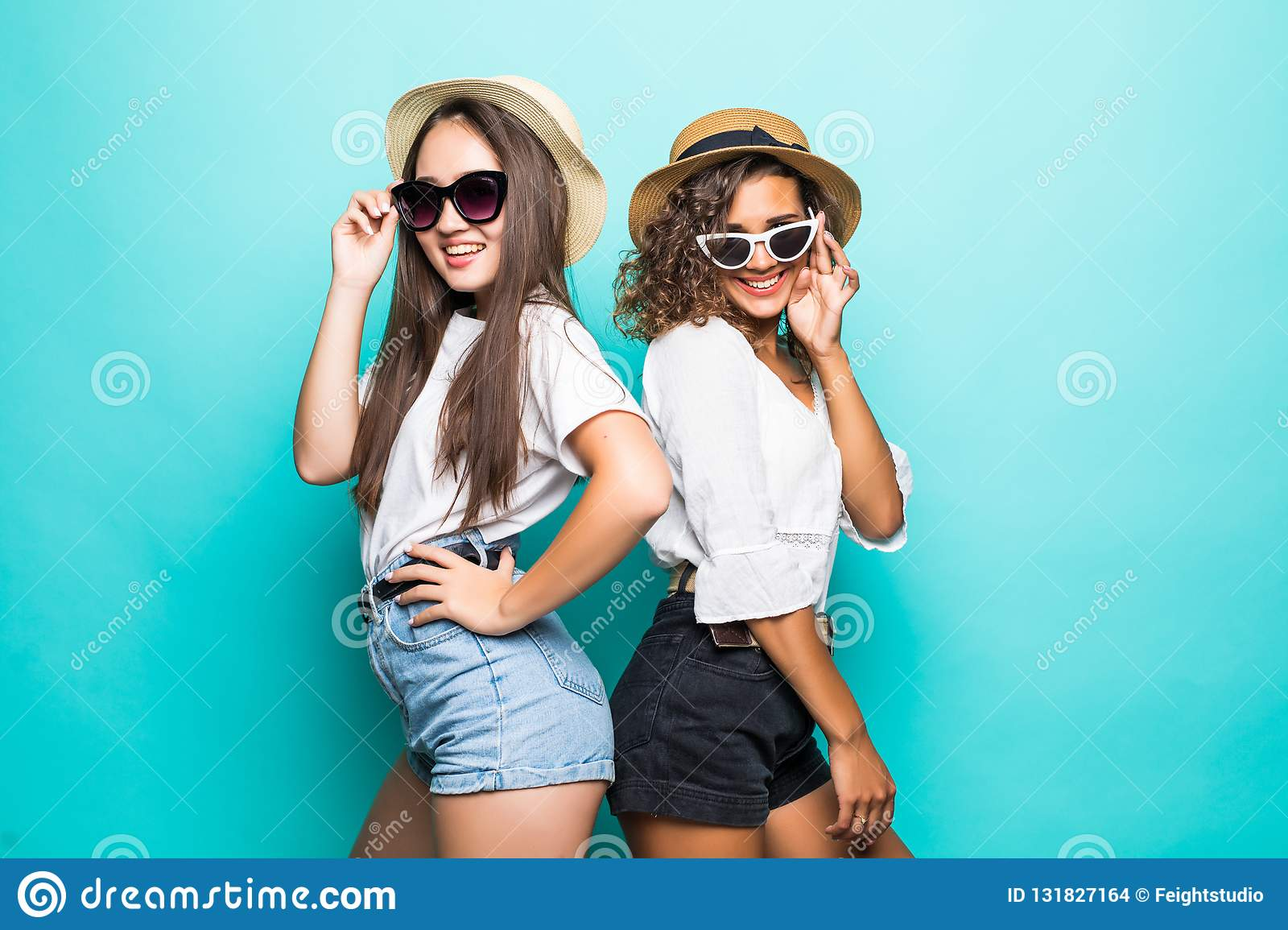 Like a sisters. Two beautiful young girl friends in sunglasses and straw hat posing with smile and have a fun on blue background