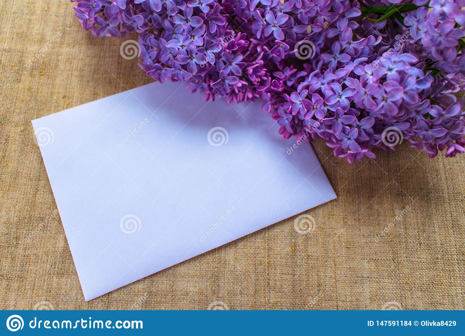 Lilac flowers in a lilac vase and an envelope with a place for an inscription. Postcard.